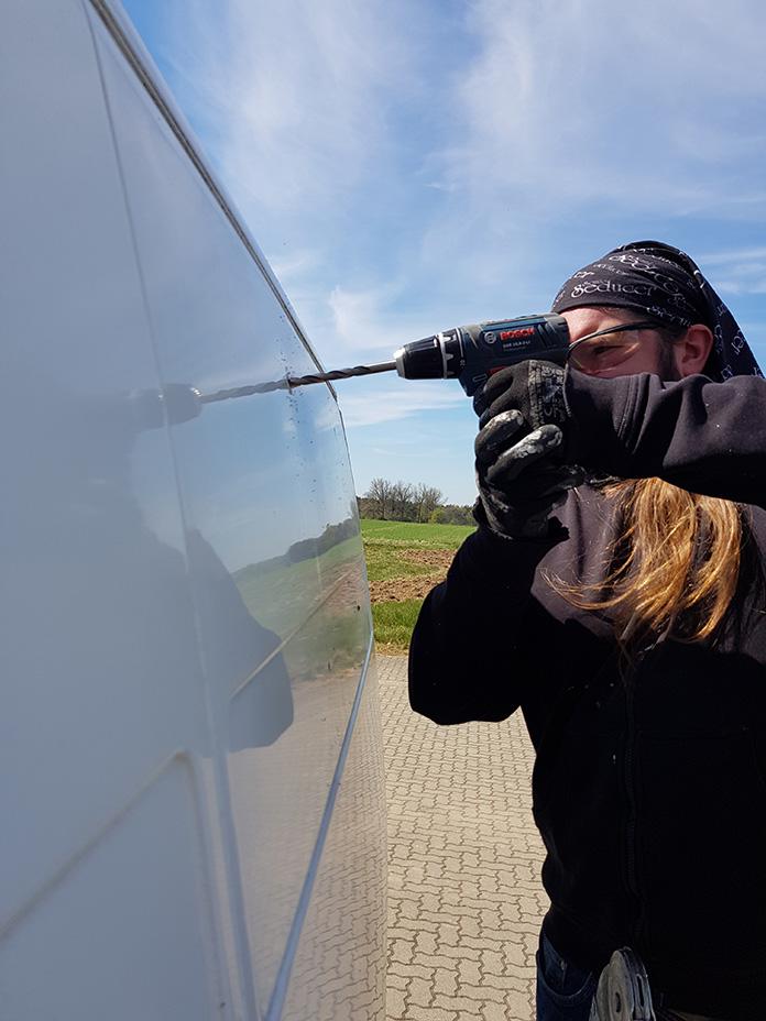 Flo bohrt ein Loch in die vorher gezeichnete Markierung für den Fenster Einbau